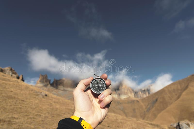 Un randonneur masculin recherche une direction avec une boussole magnétique dans les montagnes en automne Tir de point de vue ` S image stock