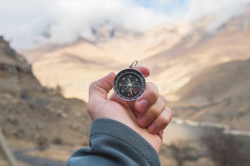 Un randonneur masculin recherche une direction avec une boussole magnétique dans les montagnes en automne Tir de point de vue ` S photographie stock