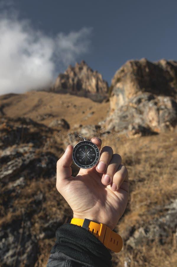 Un randonneur masculin recherche une direction avec une boussole magnétique dans les montagnes en automne Tir de point de vue ` S image libre de droits