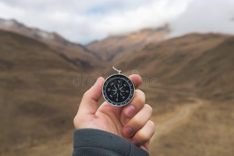 Un randonneur masculin recherche une direction avec une boussole magnétique dans les montagnes en automne Tir de point de vue ` S photo stock