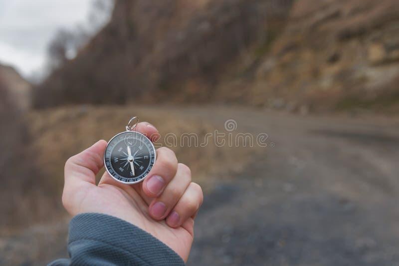 Un randonneur masculin recherche une direction avec une boussole magnétique dans les montagnes en automne Tir de point de vue ` S photo libre de droits