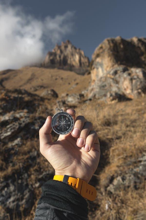 Un randonneur masculin recherche une direction avec une boussole magnétique dans les montagnes en automne Tir de point de vue ` S images libres de droits