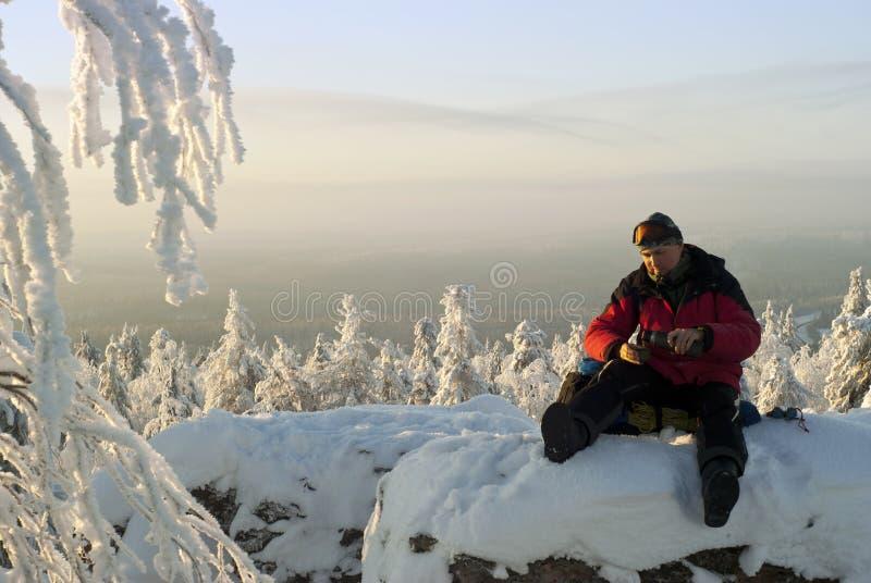 Un randonneur se verse thé sur une falaise en hiver image stock