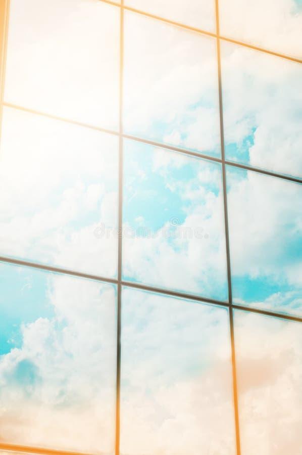 Un rascacielos o un edificio moderno en una ciudad con las nubes y la luz del sol reflejadas en Windows imagenes de archivo