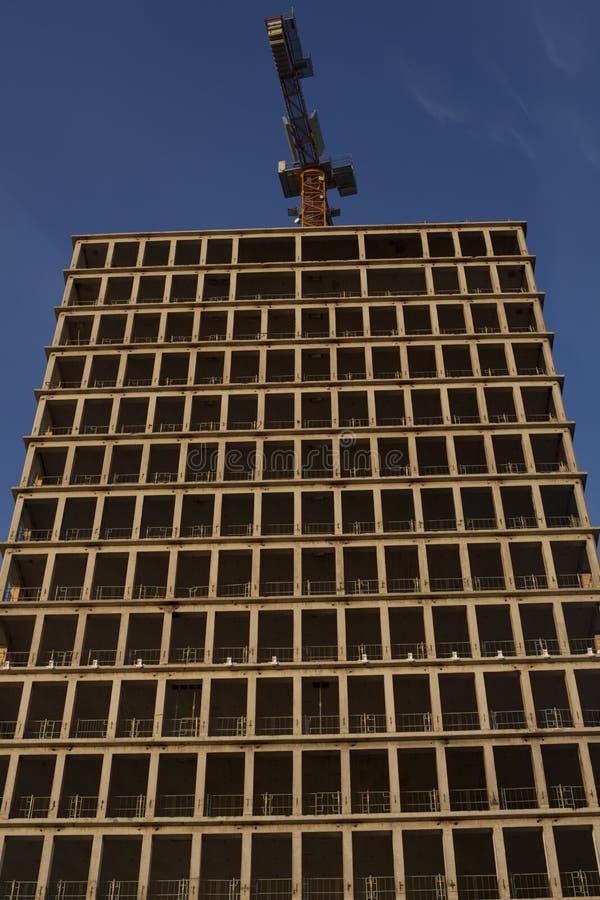 Un rascacielos que es construido con la grúa fotos de archivo libres de regalías