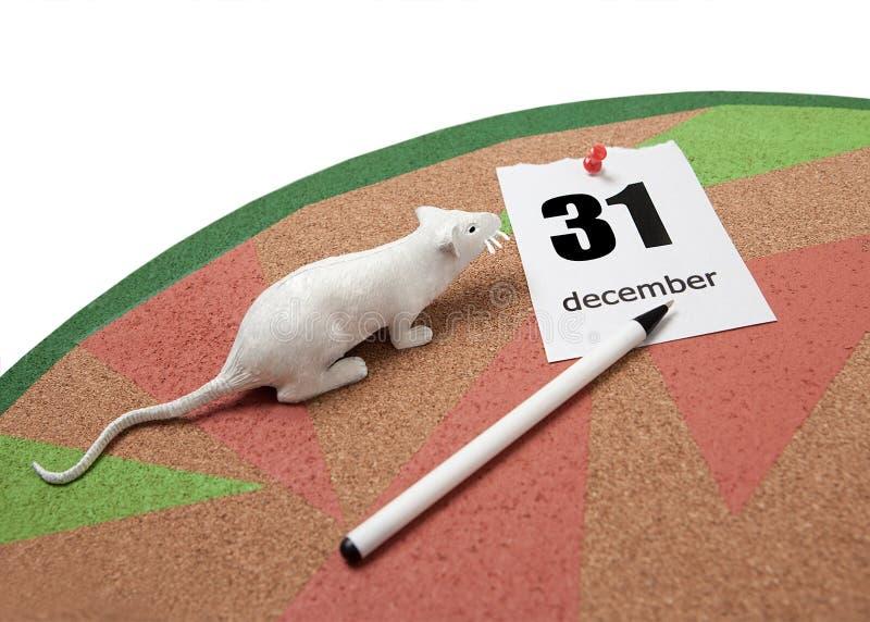 Un rat blanc à côté d'une feuille déchirée de calendrier le 31 décembre et un stylo sur un panneau de liège photographie stock