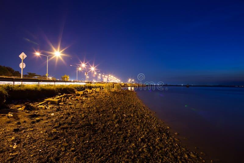 Un rato crepuscular después de la puesta del sol en el camino y la playa con el primero plano de piedra imagenes de archivo