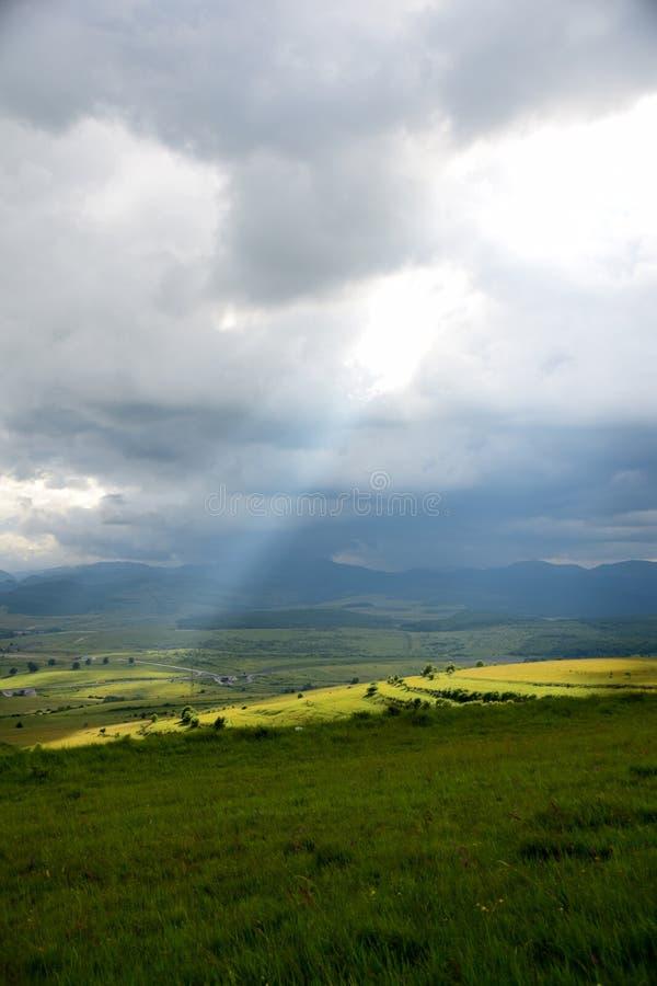 Un rayo solar que sube la tierra en un día lluvioso foto de archivo