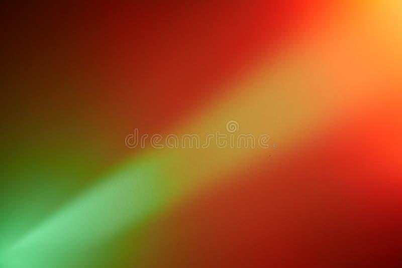 Un rayon de lumière vert clair avec une transition dans une tache rouge-clair de lumière sépare les milieux rouges et verts photo libre de droits