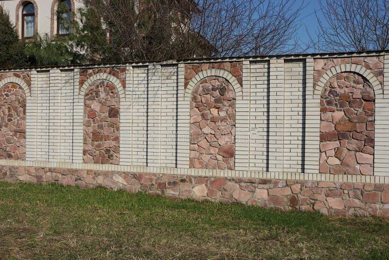 Un recinto lungo della pietra marrone e dei mattoni grigi esterni in erba verde fotografie stock