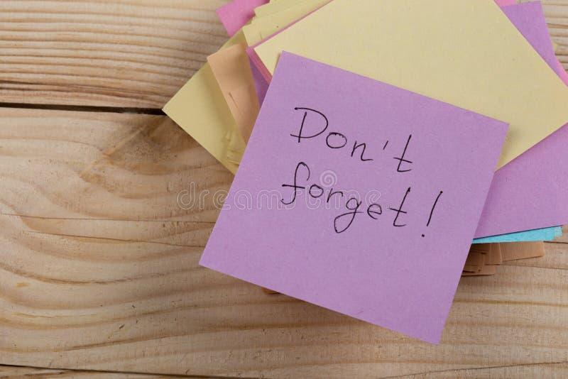 un recordatorio - don' t olvida escrito en notas de la etiqueta engomada del color sobre fondo de madera fotos de archivo libres de regalías