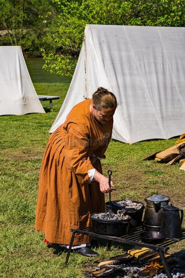 Un Reenactor femenino que cocina en el acampamento confederado imagenes de archivo