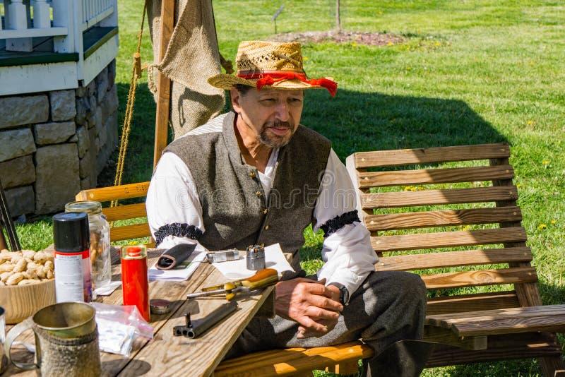 Un Reenactor masculino con un sombrero que se relaja en el acampamento confederado imágenes de archivo libres de regalías