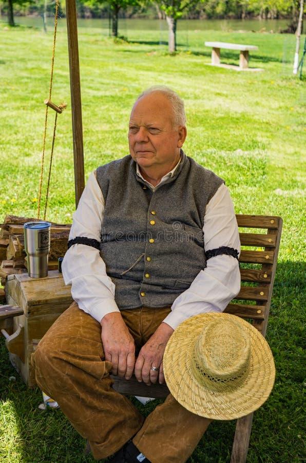 Un Reenactor masculino mayor que se relaja en el acampamento confederado fotos de archivo
