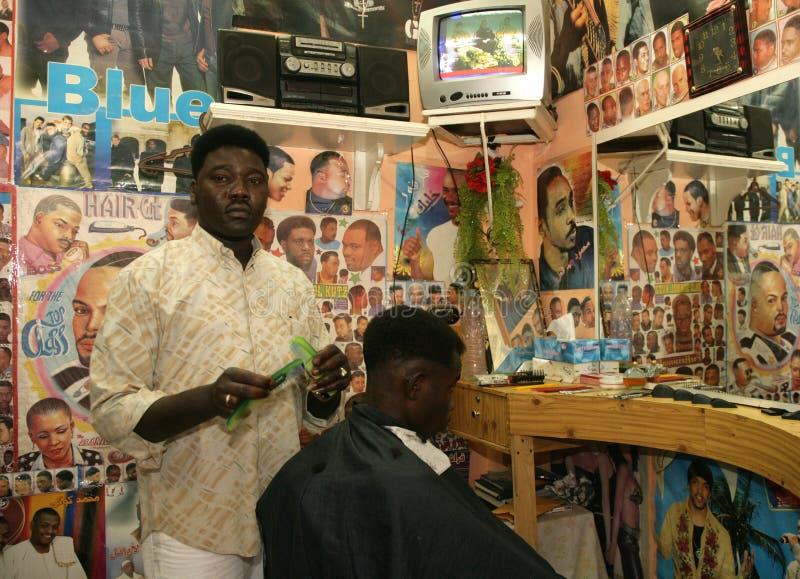 Un refugiado sudanés que trabaja en una peluquería de caballeros fotografía de archivo libre de regalías
