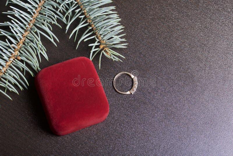 Un regalo amado Caja cerrada del terciopelo de color rojo con los pendientes del oro Cerca está un anillo de oro En un fondo oscu imagen de archivo libre de regalías