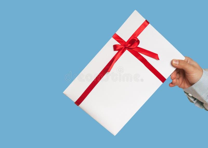 Un regalo en las manos del hombre Primer de una caja de regalo blanca y de una cinta roja Tono y el empañar Aislado en un fondo a fotografía de archivo libre de regalías