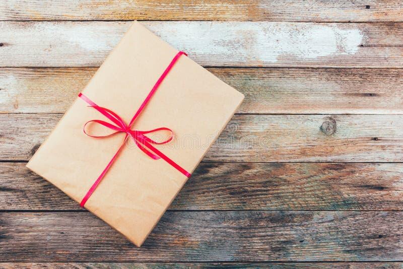 Un regalo en papel de embalaje y atado con una cinta roja en fondo retro de madera del grunge imagen de archivo