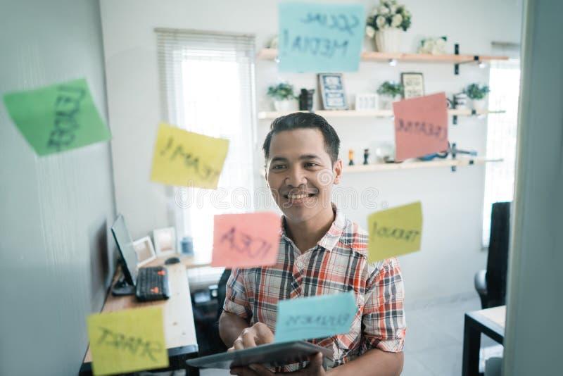 Un regard de travailleur d'homme à quelques notes de papier collent sur le mur de verre images stock