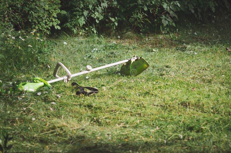 Un regolatore della falciatrice da giardino si trova sull'erba nel giardino Smussatura di erba, tagliente i prati inglesi fotografia stock