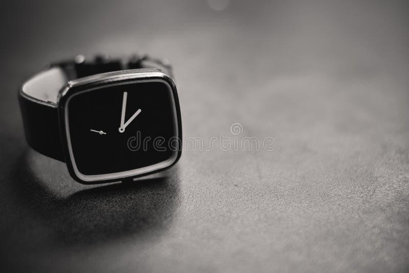 Un reloj análogo oscuro en una superficie de piedra imagenes de archivo