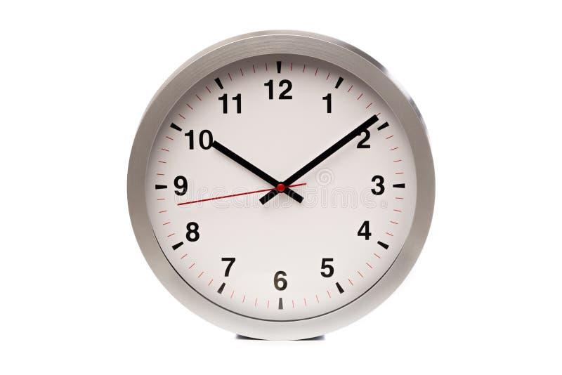 Un reloj blanco grande muestra el tiempo - imagen fotos de archivo