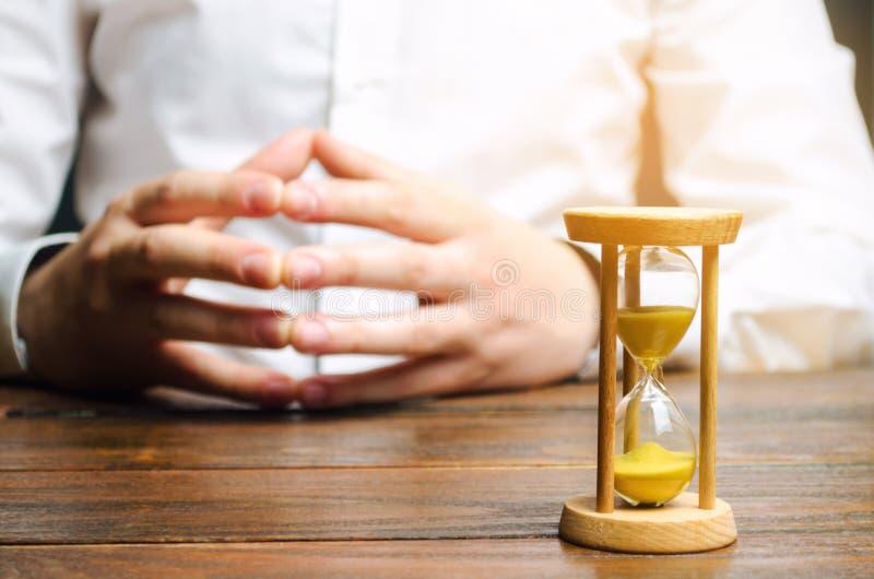 Un reloj de arena y un hombre de negocios lleva a cabo sus manos en la cerradura Concepto de la entrevista de trabajo Planificaci foto de archivo
