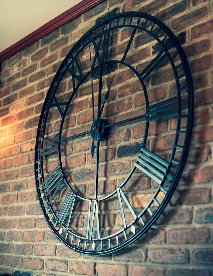 Un reloj de pared grande del metal se sienta en una pared de ladrillo fotos de archivo libres de regalías