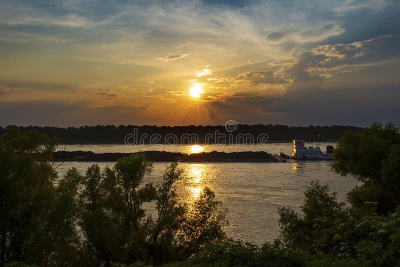 Un remolcador con barges adentro el río Misisipi en la puesta del sol cerca de la ciudad de Vicksburg en el estado de Mississipp imagen de archivo