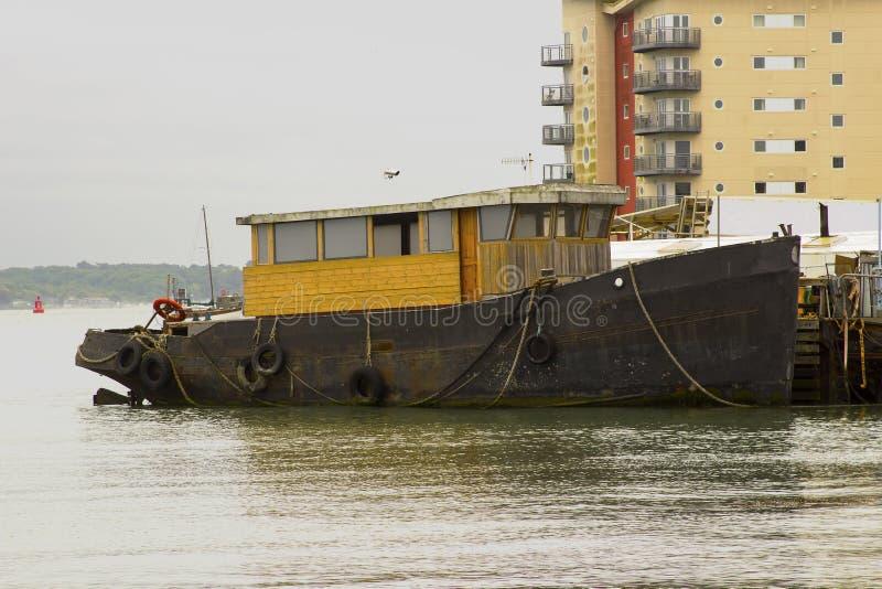 Un remolcador en curso de ser convertido a una embarcación de recreo implicada en el muelle en el puerto de Hythe en el agua de S imagen de archivo