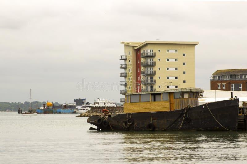 Un remolcador en curso de ser convertido a una embarcación de recreo implicada en el muelle en el puerto de Hythe en el agua de S fotografía de archivo libre de regalías