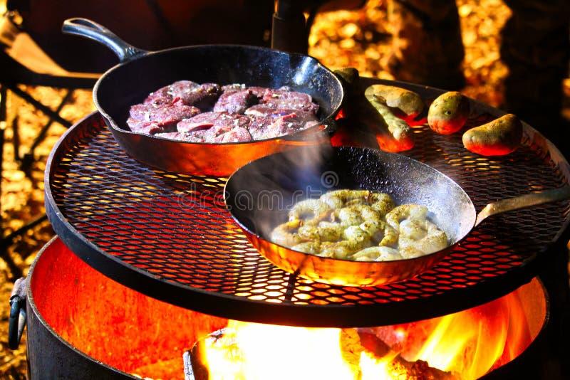 Un ressac et un repas de gazon étant fait cuire sur un feu de camp image stock