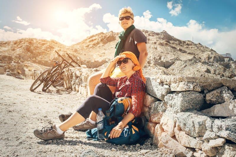 Un resto di due viaggiatori della bicicletta sulla strada della montagna fotografia stock