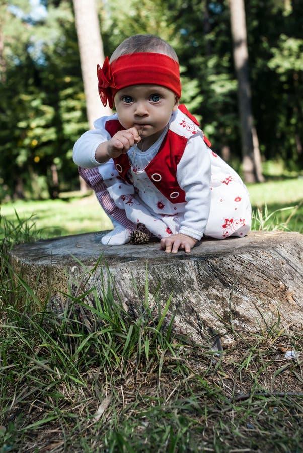 Un retrato de un bebé de nueve meses en una venda roja que se sienta en un tocón en un parque verde del verano fotos de archivo