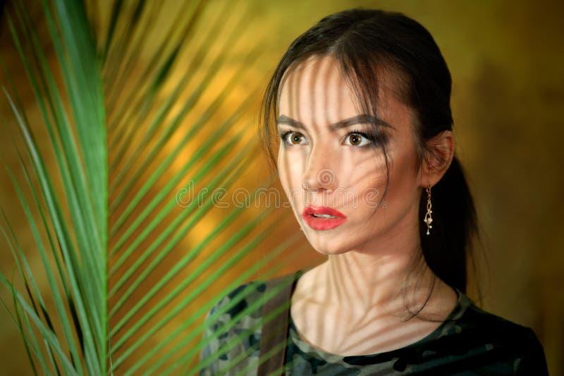 Un retrato de la chica joven con las sombras con de las hojas de palma vestidas encima como de mujer cosplay en selva fotos de archivo