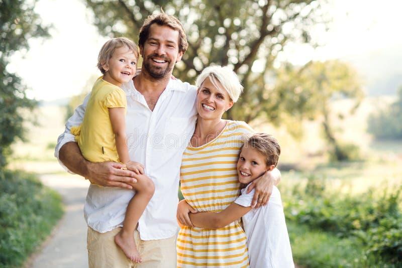Un retrato de la familia joven con los pequeños niños en naturaleza soleada del verano fotografía de archivo