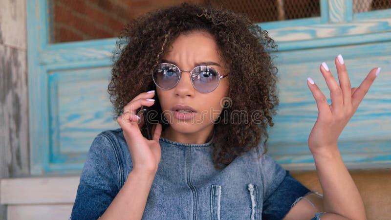 Un retrato de la mujer afroamericana que habla por el teléfono con la cara infeliz imagen de archivo