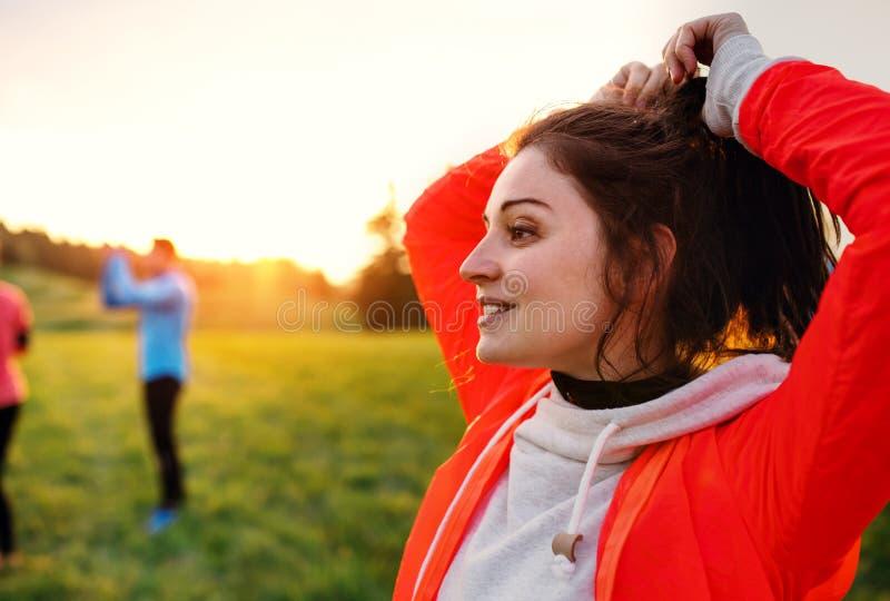 Un retrato de la mujer joven con el grupo de personas que hace ejercicio en naturaleza imagen de archivo libre de regalías