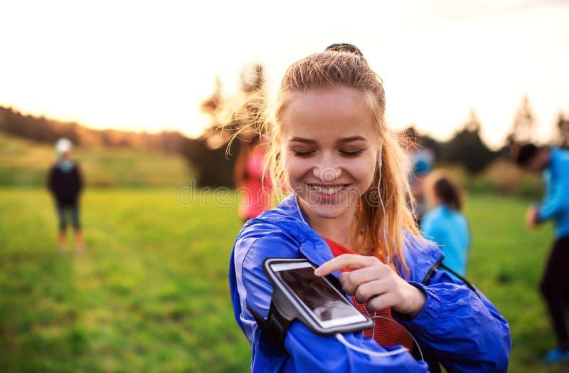 Un retrato de la mujer joven con el smartphone que hace ejercicio en naturaleza imagenes de archivo
