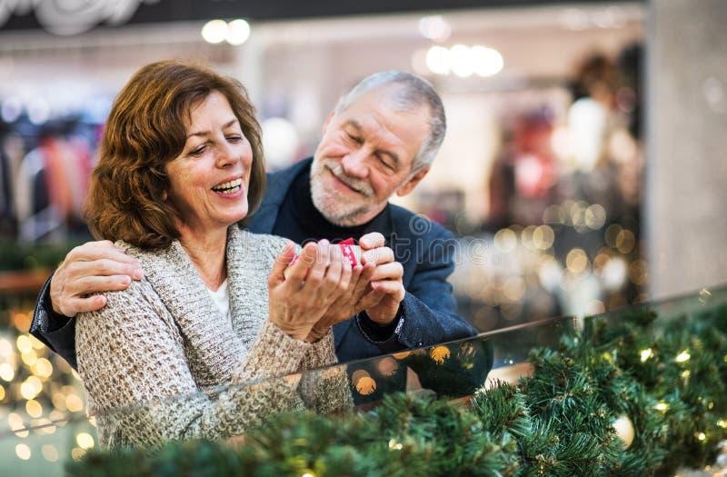 Un retrato de pares mayores con un presente en centro comercial en el tiempo de la Navidad fotografía de archivo