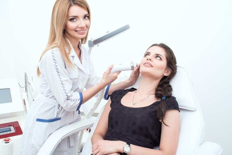 Un retrato de un cosmetologist atractivo de la señora que proporciona el tratamiento del facial del laser foto de archivo