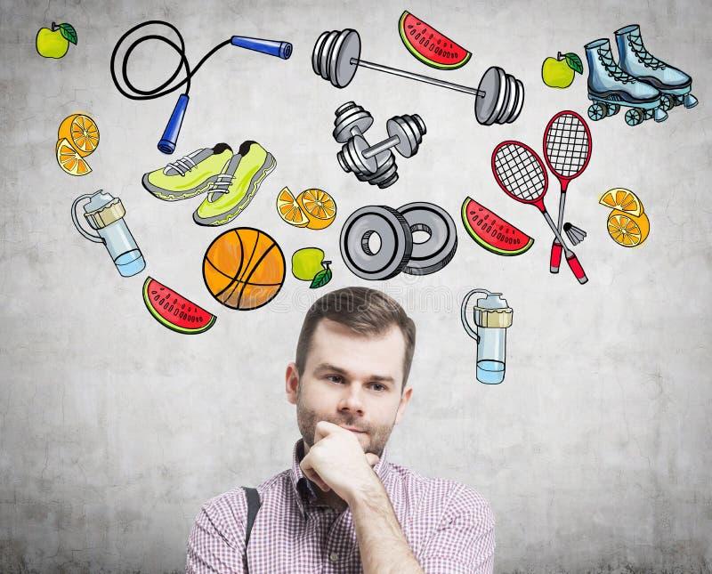 Un retrato de un hombre hermoso de sueño que está pensando en su opción de la actividad del deporte Los iconos coloridos del depo fotografía de archivo libre de regalías