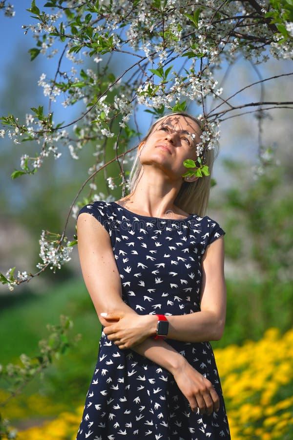 Un retrato de una chica joven hermosa en un vestido azul en el jardín con los manzanos blosoming teniendo la diversión y goce foto de archivo