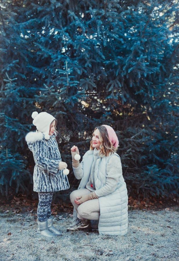 Un retrato de una familia feliz: una mujer hermosa joven con su pequeña hija linda que camina en el parque de la ciudad del invie imagen de archivo