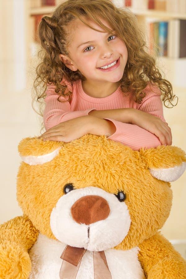 Un retrato de una muchacha bonita joven que sonríe y que presenta sobre su cabeza del oso de peluche s en un fondo de la oficina  imágenes de archivo libres de regalías