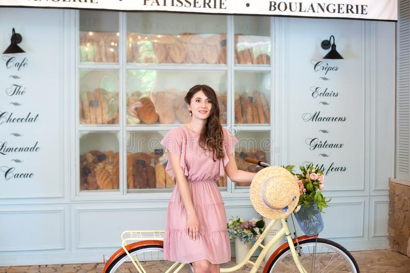 Un retrato de una muchacha hermosa en un vestido rosado se está colocando con una bicicleta retra amarilla en el fondo de una cal fotos de archivo