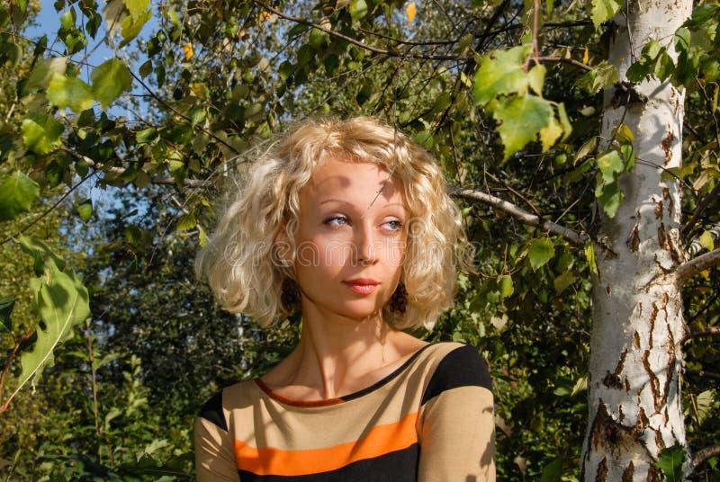 Un retrato de una mujer bastante joven con un pelo rubio rizado y ojos azules, colocándose cerca de un abedul en el parque fotos de archivo
