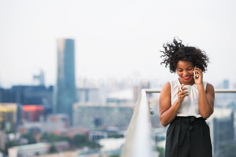 Un retrato de una mujer con café y del smartphone que se coloca en una terraza foto de archivo
