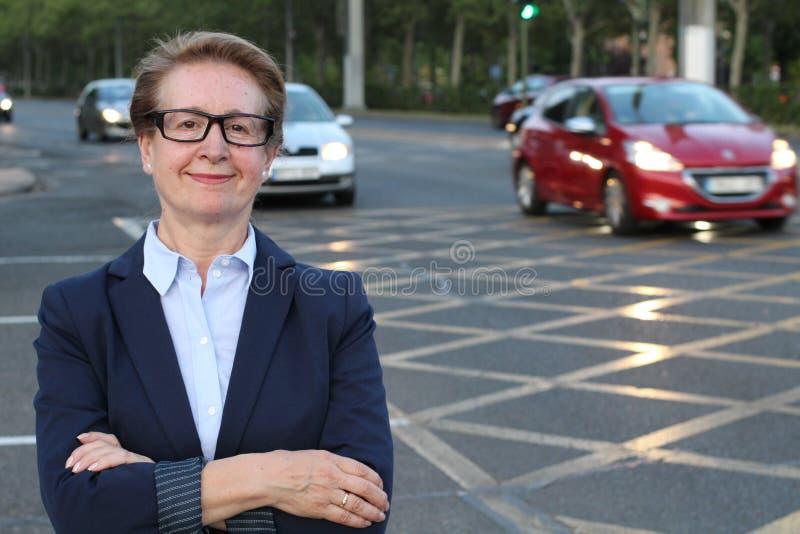 Un retrato de una mujer de negocios de mirada satisfecha con sus brazos cruzó en una calle ocupada de la ciudad con las porciones foto de archivo