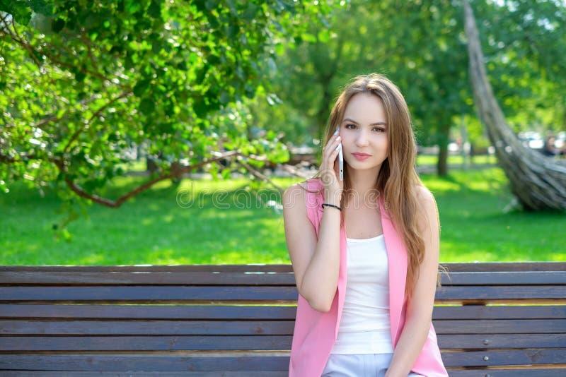 Un retrato de una mujer hermosa sonriente que habla en el teléfono imagen de archivo libre de regalías